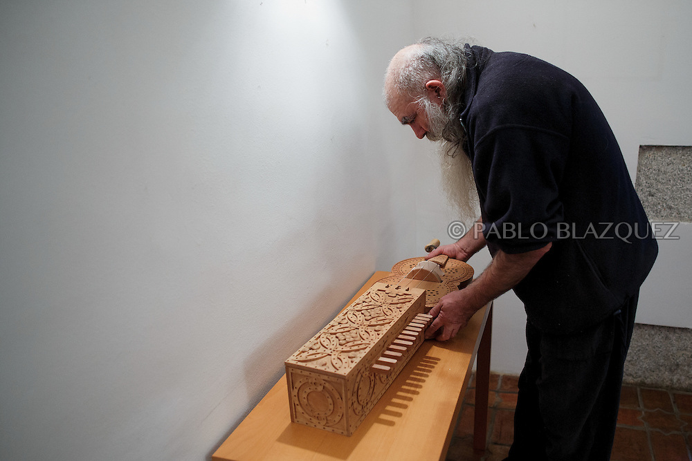 02/12/2016. Jesus Reolid holds an organistrum as he prepares an exhibition of musical instruments from medieval times recently made by luthiers at the Santa María la Real de Valdeiglesias Monastery on December 2, 2016 in Pelayos de la Presa, Madrid province, Spain. The Collegiate of Santa María la Mayor is a Romanesque architecture church built during the 12th and 13th centuries. Recents restorations of the Church discovered many details on its sculptures. Then luthiers started the project 'De la piedra a la madera' to recover and to reproduce the instruments displayed on the North Gate. (© Pablo Blazquez)