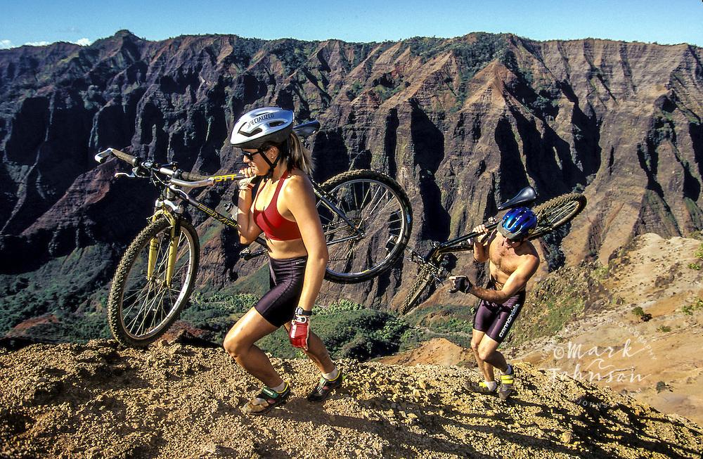 Hawaii, Kauai, Waimea Canyon, mountain biking couple carrying bikes up ridge