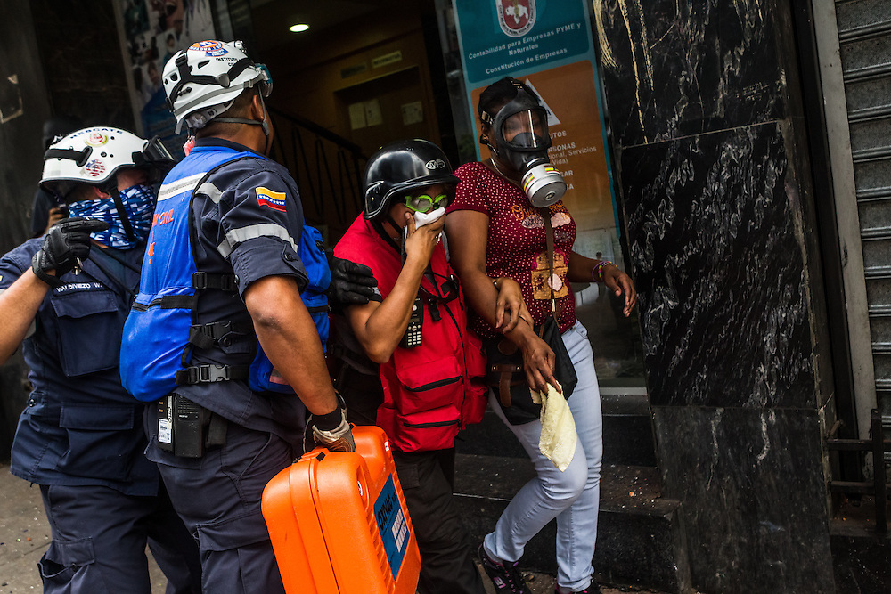 CARACAS, VENEZUELA - APRIL 17, 2014: A pregnant woman is evacuated by paramedics from a residential building because she could not breathe because of excess amounts of tear gas entering her apartment, while anti-govenrment protesters and the National police clashed in the street below. Venezuela has been shaken by more than two months of sometimes violent protests set off by frustration with rampant crime, one of the world's highest inflation rates, shortages of basic goods and a government crackdown on dissent. Hundreds of people have been detained for participating in the protests, or picked up just from being near them, and many people have claimed to have been physically assaulted while detained. CREDIT: Meridith Kohut for The New York Times