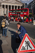 A man next to a Man At Work traffic sign, stands up after crouching on the bust street in the City of London.