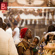 A woman carrying her child walks through a pavilion at the 22nd Salon International de l'Artisanat de Ouagadougou (SIAO) in Ouagadougou, Burkina Faso on Saturday November 1, 2008.