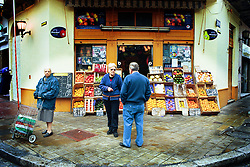 BUENOS AIRES, ARGENTINA:  Locals stand outside a fruit shop in Buenos Aries, Argentina. (Photo by Ami Vitale)
