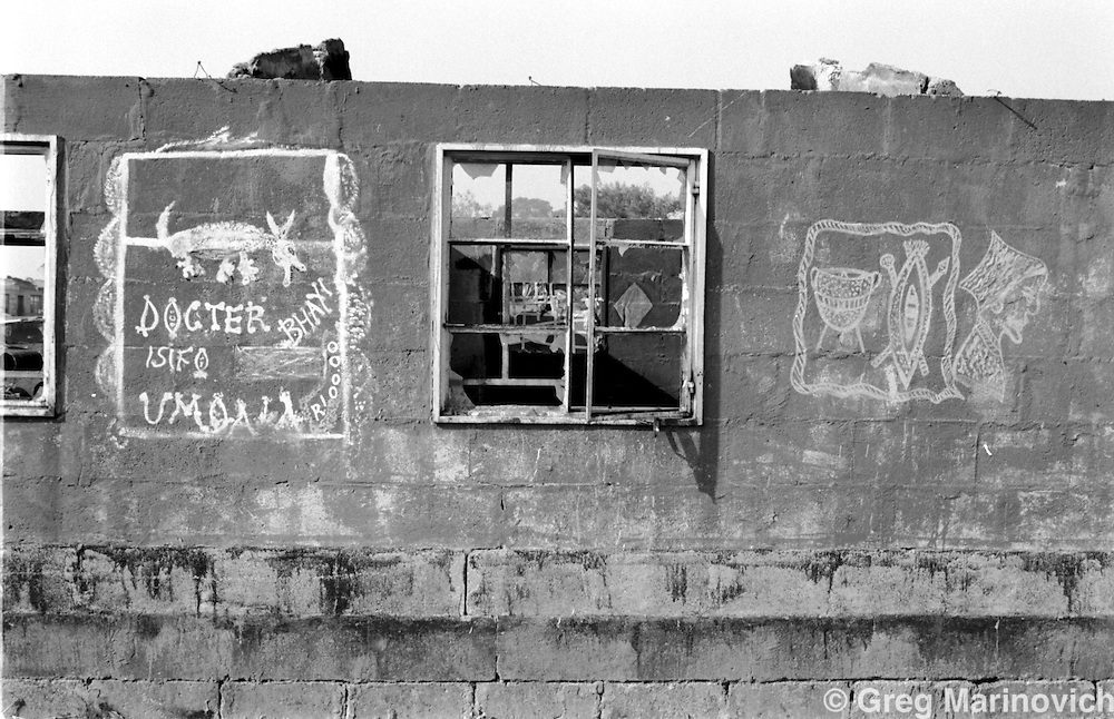 The burnt shell of a hostel in Tokoza Oct 1990, on the East Rand some 20km East of Johannesburg, with the signs advertising a tradiional healer. The migrant workers' hostel was later destroyed in the clashes between Inkatha Freedom Party supporters and those of the African National Congress. (Photo by Greg Marinovich)
