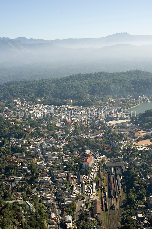 Kandy, the second largest city in Sri Lanka. In the centre is the Railway station and in the far distance Kandy lake with the forest called Udawattakelle covering the hill behind the Temple of the Tooth. Running parallel to the railway lines is the old Kandy-Peradeniya Road.