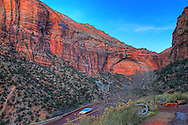 An arch is formed into the rock walls of the surrounding canyon as State Route 9 winds it's way through Zion National Park in southern Utah. A car is seen streaking down the mountain along the road. This view, taken close to sunset in the popular National Park, is an HDR image, created with several digital captures.