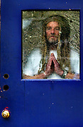 Jack Tafari prays for strength at the rear door of the community room at Dignity Village in Portland, OR. He, as the spiritual and motivational leader, is 1 of 65 homeless people who have taken up residence on the leaf recycling land near the airport with the city's permission. They are being asked to leave again by October and find a new home.