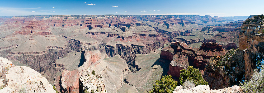 Powell Point, South Rim of Grand Canyon National Park, Arizona, USA. Grand Canyon began forming at least 5 to 17 million years ago and now exposes a geologic wonder, a column of well-defined rock layers dating back nearly two billion years at the base. While the Colorado Plateau was uplifted by tectonic forces, the Colorado River and tributaries carved Grand Canyon over a mile deep (6000 feet / 1800 meters), 277 miles (446 km) long and up to 18 miles (29 km) wide. (Panorama stitched from 3 photos.)
