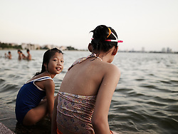 Vietnamese people bath in west lake of Hanoi by a hot summer day. Despite high pollution level of waters, hanoians enjoy wade when hot season comes. Hanoi, Vietnam, Asia