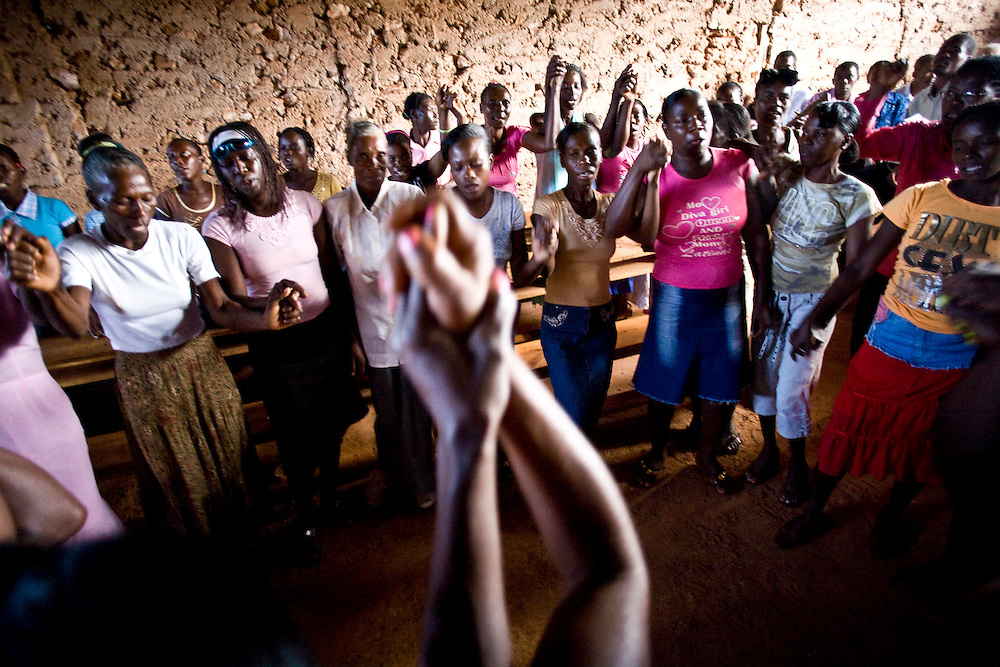 Chemen Lavi Miyò clients sing and hold hands during their program graduation. During the program clients work together and rely on one another for support.  La Gonave, Haiti. Photo by Ben Depp. 1/30/2009.