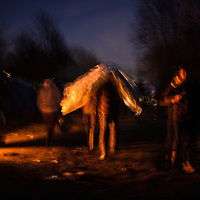 Migrant carring a matreass on his head during the night at the Grande Synthe camp, France. FEDERICO SCOPPA/CAPTA