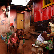 Khadija braiding Madlyn's hair amongst friends and neighbours, Kroo Bay, Freetown, Sierra Leone.