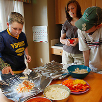 Zachary Frantzen (L) prepares dinner as her mother Leslie (C) and brother Spencer watch in Longmont, Colorado July 19, 2010.  Zachary, 10, is in the Shapedown Program which is part of the child and teen weight management program at The Children's Hospital in Aurora. REUTERS/Rick Wilking (UNITED STATES)