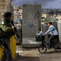 A Palestinian boy rides his bike past Israeli Border Police Officers as he cross a checkpoint during the annual parade marking the Jewish holiday of Purim, in the divided West Bank town of Hebron, Sunday, March 28, 2010. The festival of Purim commemorates the rescue of Jews from genocide in ancient Persia. Photo by Olivier Fitoussi