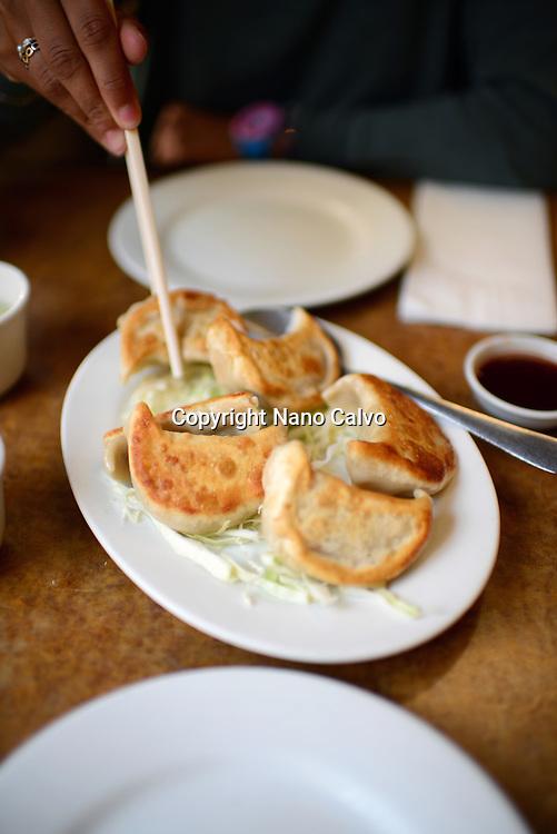Woman eating dumplings (Guotie) in Hong Kong Clay Pot Restaurant in Chinatown, San Francisco