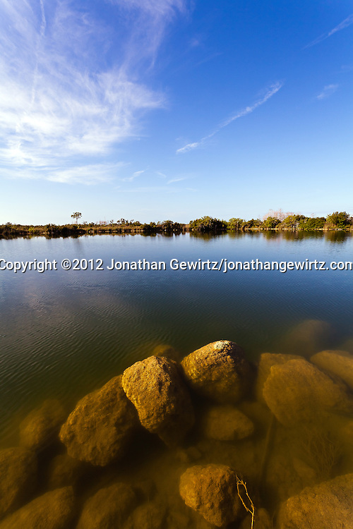 A tranquil pond with submerged rocks just under the surface, in Everglades National Park, Florida. WATERMARKS WILL NOT APPEAR ON PRINTS OR LICENSED IMAGES.