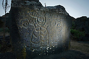 """The shape of a shaman or mystreious mythical figure stand in relief - etched into a rock on the """"Temani Pesh-wa"""" trail (also """"written on rock"""" trail) in Columbia Hills State Park on the Washington Side of the Columbia River Gorge. This petroglyph was removed from the famous """"Petroglyoh Canyon"""" along the Columbia River before it was flooded by construction of The Dalles Dam in 1957. The Army Corps Of Engineers stored the rock art until 2004 when Temani Pesh-wa trail was built."""