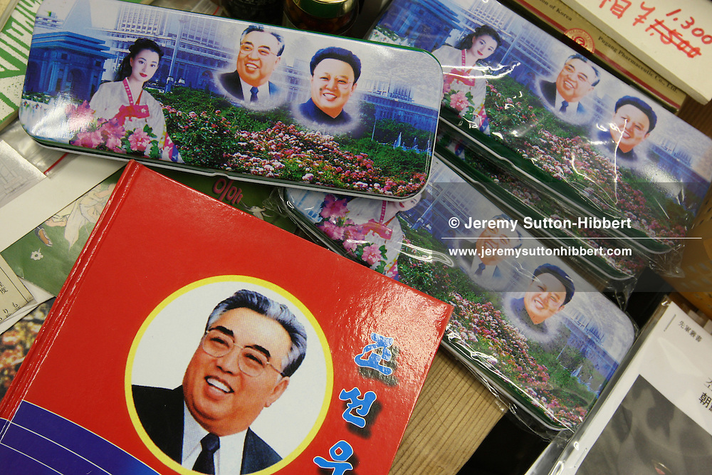 """Mr. Jun Miyagawa, of the Rainbow Trading Company ( a North Korean speciality bookstore) shows off the North Korean products he has for sale ( including Kim Il Sung badges, North Korean bank notes, football memorabilia, cigarettes, and North Korean propaganda posters and genuine North Korean military uniforms), in his book store in Jimbocho district,  Tokyo, Japan, Friday, Aug. 17, 2007. All the products come via a contact of Mr Miyagawa's in China. The posters are individually painted and range in price from ¥50,000-¥150,000, the Kim Il Sung badges cost approximately JPN Yen 4,000. The products are bought mainly by Japanese 'North Korea fans"""", or as Mr. Miyagawa put it """"by Japanese who have a healthy obsession with North Korea""""."""