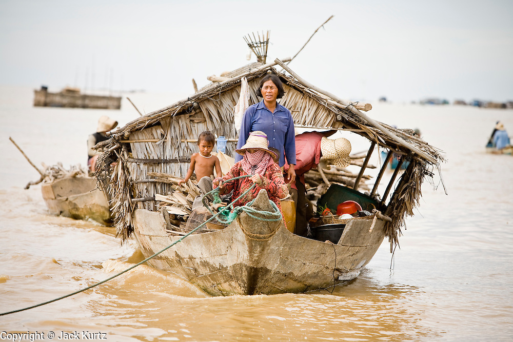 28 JUNE 2006 - CHONG KHNEAS, SIEM REAP, CAMBODIA: A motor boat hauls a houseboat to the floating village of Chong Khneas, at the northwest end of Tonle Sap Lake, Cambodia's vast inland sea. More than 2,500 people live on the lake in houses that move as the lake expands and contracts with the seasons. During the dry season the lake covers about 2,500 square kilometers. At the peak of the rainy season the Tonle Sap swells to more than 13,000 square kilometers. Photo by Jack Kurtz / ZUMA Press