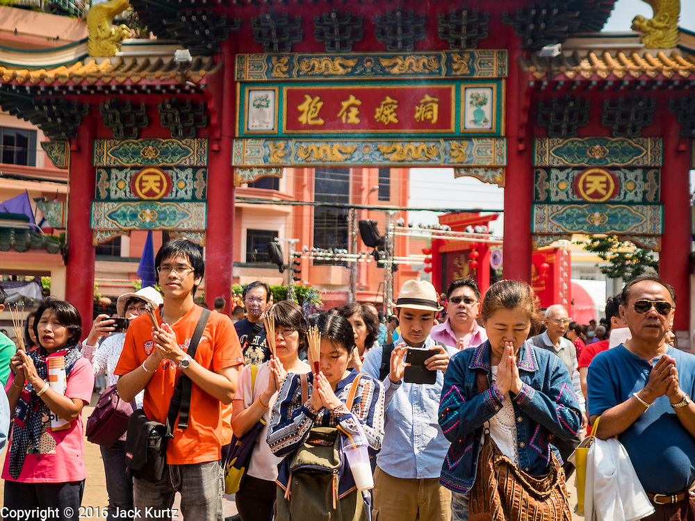 """08 FEBRUARY 2016 - BANGKOK, THAILAND: People pray during Chinese New Year observances at Kuan Yim Shrine in Bangkok's Chinatown district, during the celebration of the Lunar New Year. Chinese New Year is also called Lunar New Year or Tet (in Vietnamese communities). This year is the """"Year of the Monkey."""" Thailand has the largest overseas Chinese population in the world; about 14 percent of Thais are of Chinese ancestry and some Chinese holidays, especially Chinese New Year, are widely celebrated in Thailand.       PHOTO BY JACK KURTZ"""