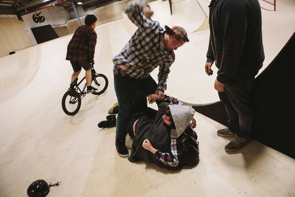 Three guys play fight at the side of one of the vast indoor ramps within Unit 23.