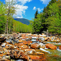 Ellis River Rapids in White Mountain National Forest near North Conway, New Hampshire<br /> There are two scenic byways looping through the White Mountain National Forest&rsquo;s. Also winding through the 750,000 acres is the Ellis River. The 17-mile flow begins at the 6,288 foot peak of Mount Washington. Nearby are other mountains named after eight presidents plus notables like Ben Franklin and Sam Adams. Among this gorgeous scenery are quaint villages, museums, covered bridges and tranquil landscapes.