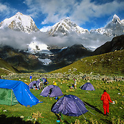 "Trekkers camp in a green pasture at 13,600 feet elevation in the Cordillera Huayhuash, Andes Mountains, Peru, South America. Yerupaja Grande (left, east face, 6635 m or 21,770 ft) is the second-highest peak in Peru, highest in Cordillera Huayhuash, and highest point in the Amazon River watershed. At center is Yerupaja Chico (20,080 feet). On right is Mount Jirishanca (""Icy Beak of the Hummingbird,"" 6126 m or 20,098 feet). Published by Scholastic Inc in 2008 and 2013 classroom paperback ""Left to Die."" Published in ""Light Travel: Photography on the Go"" book by Tom Dempsey 2009, 2010."