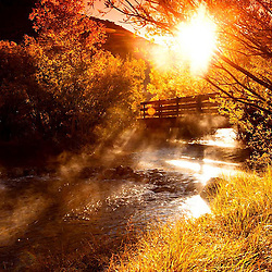Sunrise over bridge on river.