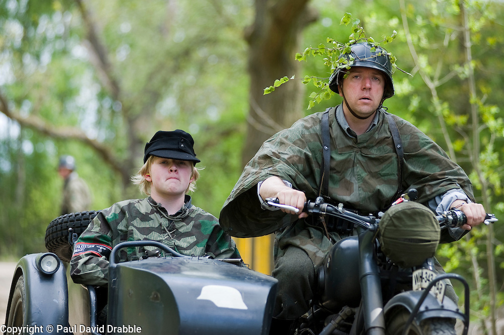 Reenactors from Northern World War Two Association, portraying members of the Grossdeutschland division riding a motorcycle and sidecar combination during a 24hr private exercise, held at Sutton Grange, near Ripon in Yorkshire. The white steel helmet or Stahlhelm marked on the front of the sidecar is the Gro&szlig;deutschland Division tactical symbol, <br />