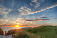 The sun sets over Cape Cod Bay, with the dunes of Cold Storage Beach in the foreground.