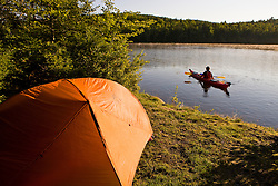 A man kayaks on the Androscoggin River next to a remote campsite at Mollidgewock State Park in Errol, New Hampshire.