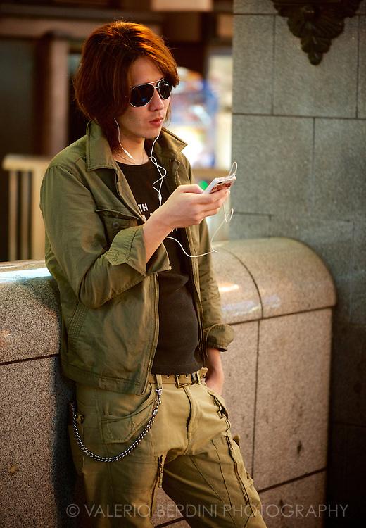 A guy standing on nampa-bashi bridge listening to music on his iPod. Osaka, Japan 2013