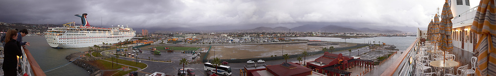 """Panorama of the Ensenada harbor in Mexico on a grey and raining day from the deck of the MV World Odyssey. The other cruse ship is the Carnival Imagination. Once all of the students, faculty, staff, and life long learners were aboard we would be ready to begin the 102 day """"round the world"""" Semester at Sea Spring 2016 Voyage. Composite of nine images taken with a Leica T camera and 23 mm f/2 lens (ISO 250, 23 mm, f/2, 1/80 sec). Panorama stitched using AutoPano Giga Pro."""