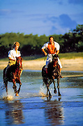 Couple riding horses on the beach