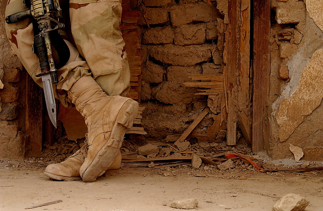 """A member of the U.S. Army 3/187th Scouts from Fort Campbell, Kentucky, takes a break at a bombed out building on April 12, 2002  at  Kandahar Air Base, Afghanistan. The Scouts, and the Lord Strathcona's Force (Royal Canadian) Reconnaissance Squadron """"RECCE"""" 2TP from Edmonton Canada along with the and Afghanistan Military Forces (AMF) have been conducting surveillance of the outer perimeter of the Air Base. This small multinational force is positioned at the North Tower on the outer perimeter outside of Kandahar airport during Operation Enduring Freedom. Their mission is to play a surveillance role on the outer perimeter with the capability of providing direct fire support. — © SSgt Jeremy Lock/"""