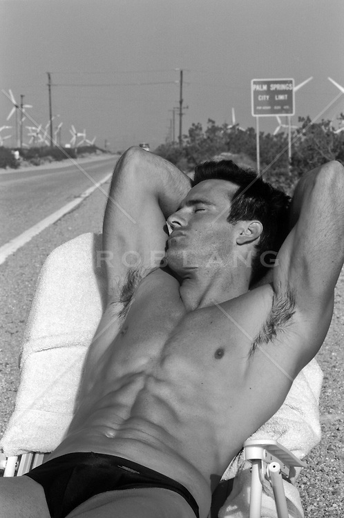 sexy man on a beach chair on the side of the road in Palm Springs, CA