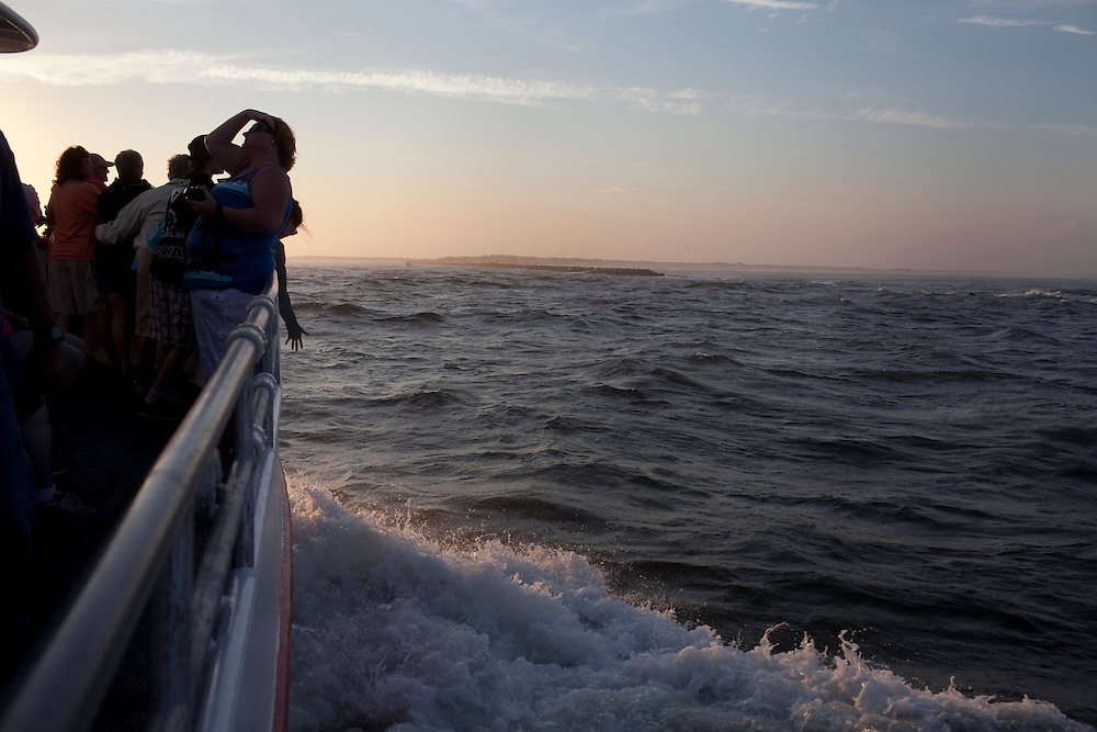 Long Beach Island, NJ - June 29, 2013 :  Visitors on Miss Barnegat Light sunset cruise watch the sun set over Long Beach Island, NJ on June 29, 2013. People are returning to the beaches for the summer after recovery efforts post Superstorm Sandy.
