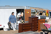large woman leaning against a trailer of junk at a flea market in South Carolina