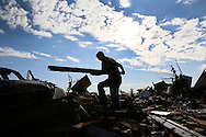 Jon Booth carries debris from his mothers tornado-destroyed home across the street from the Plaza Towers elementary school in Moore, Oklahoma May 22, 2013. A massive tornado tore through a suburb of Oklahoma City, wiping out whole blocks and killing at least 24.   REUTERS/Rick Wilking (UNITED STATES)