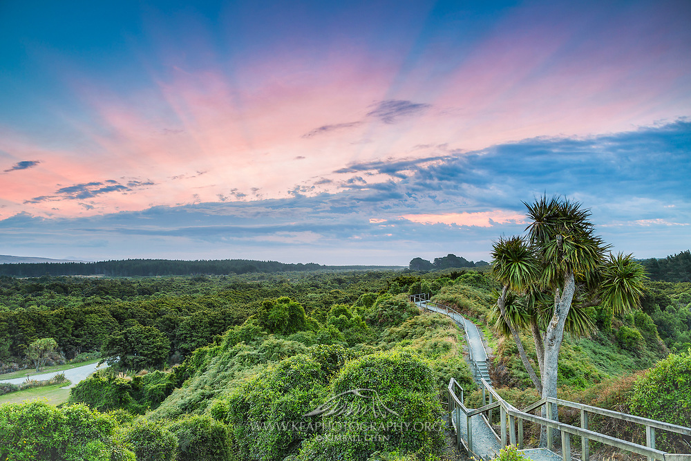 A radiant sunset breaks through a wall of cloud sitting over the horizon, as viewed from the top of Hatch's Hill, Sandy Point, Invercargill, New Zealand.