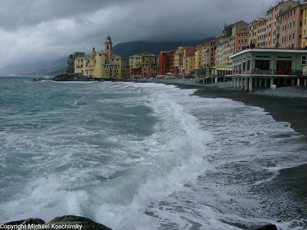 Old city at ligurian coast, breaking waves in forground, rainy day
