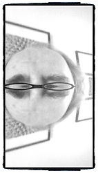 monochrome abstract image of forehead, eyebrows, and glasses reflection
