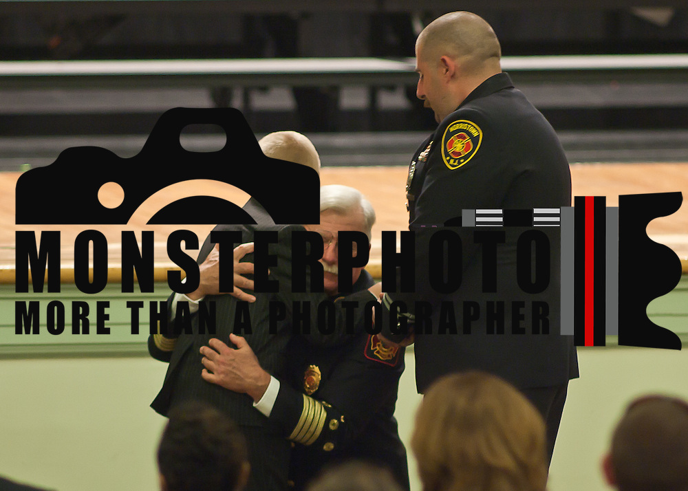10/16/11 Wilmington DE:  Deputy Chief Allen J. Huelsenbeck (Middle) hugs his grandson during Wilmington Fire Academy promotion Ceremony Monday, Oct. 17, 2011 at P.S. Dupont Middle school in Wilmington Delaware...Funding for 13 of the 14 members of the current class is coming from a controversial grant approved by City Council this past spring...The 13 men and one woman make up the 36th Wilmington Fire Department Academy, which will bring the department up to 173 members...The News Journal/SAQUAN STIMPSON