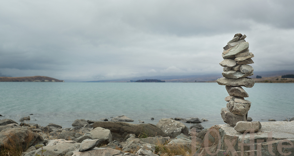 Zen stones piled up overlooking Lake Tekapo, New Zealand with Aoraki / Mt Cook obscured by clouds. The image is available for commercial licensing through Arcangel Images. ID# AA164495 . Contact LOxArte for Fine Art Prints.