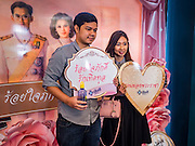 "14 FEBRUARY 2017 - BANGKOK, THAILAND: A newly married couple poses for a photo in front of Bhumibol Adulyadej, the Late King of Thailand, and his wife, Queen Sirikit in the Bang Rak district in Bangkok. Bang Rak is a popular neighborhood for weddings in Bangkok because it translates as ""Village of Love."" (Bang translates as village, Rak translates as love.) Hundreds of couples get married in the district on Valentine's Day, which, despite its Catholic origins, is widely celebrated in Thailand.      PHOTO BY JACK KURTZ"