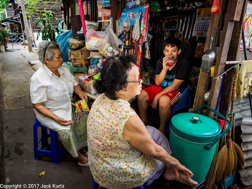 07 APRIL 2017 - BANGKOK, THAILAND:  Women who live in Pom Mahakan sit in front of a snack stand in the old fort and socialize. The final evictions of the remaining families in Pom Mahakan, a slum community in a 19th century fort in Bangkok, have started. City officials are moving the residents out of the fort. NGOs and historic preservation organizations protested the city's action but city officials did not relent and started evicting the remaining families in early March.             PHOTO BY JACK KURTZ