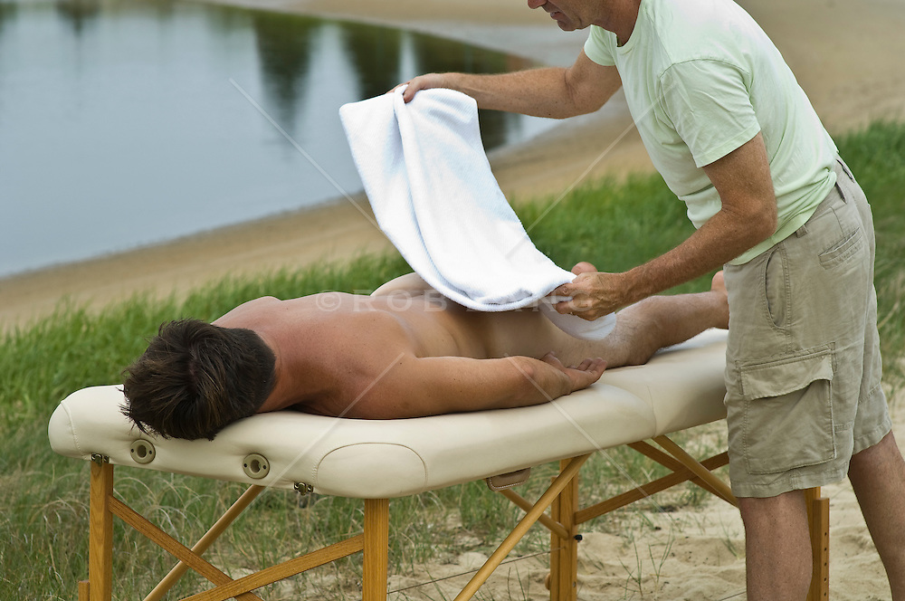 Nude Man Getting A Towel Placed Over Him By Massage Therapist