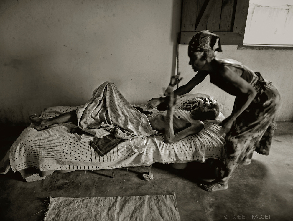 Batey 50, Dominican Republic- A woman tends to her ill husband in their small hut at workers' community on a sugarcane plantation known as Batey 50. These villages, bateyes, often lack clean water, adequate housing, medical services, and other basic sanitary services. (Photo by Robert Falcetti)
