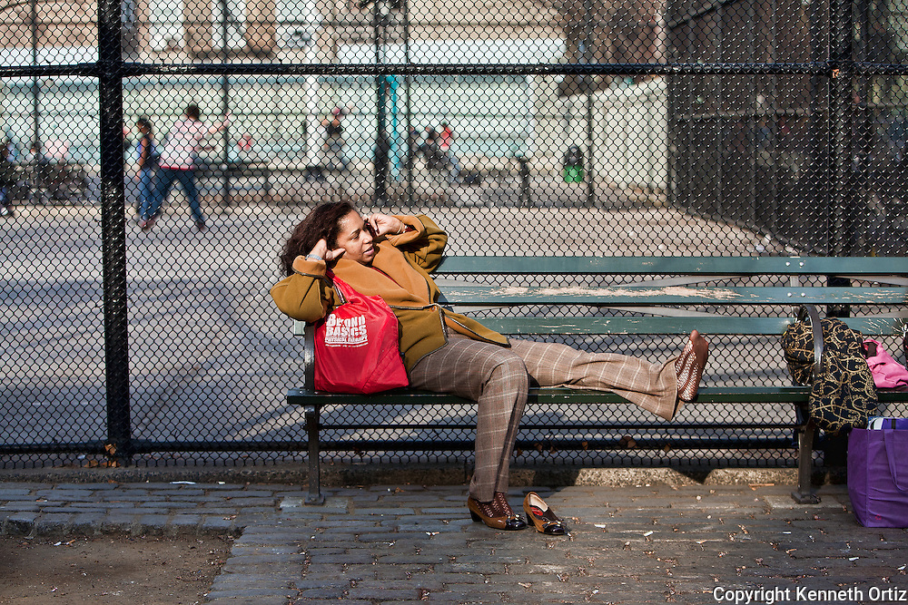 During an unusually warm day in February, and woman takes a moment to relax and unwind on a bench on Spring Street in Downtown SoHo, New York City.