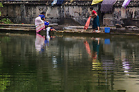 Washing Women at Kerala, using tradtional methods of available water, stones and soap these women do their daily laundry on a pond without benefit of electrical washing machines.