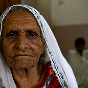 Dai Ghair Bibi sits in her living room. A traditional birth attendant for more years then she can recall, she most fondly remembers delivering the babies within her own family. Koohi Goth, Karachi, Pakistan, 2011